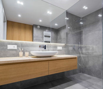 Modern bathroom with wooden countertop, shower, basin and big mirror